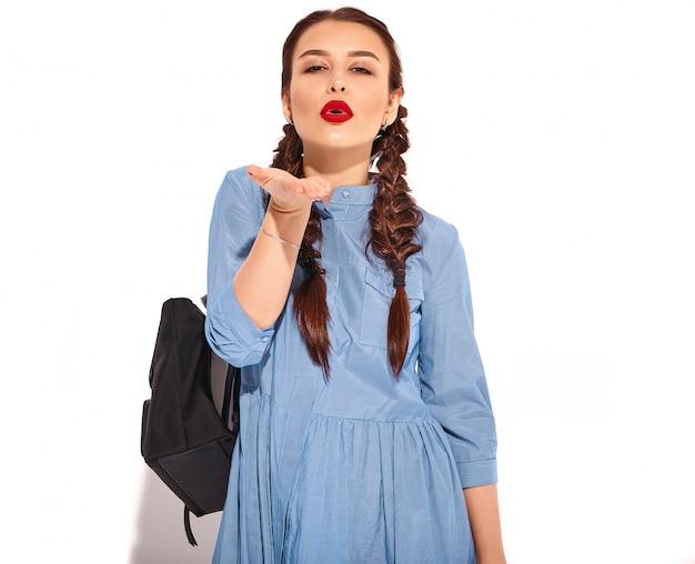 Porträt des jungen glücklichen lächelnden frauenmodells mit hellem make-up und den roten lippen mit zwei zöpfen in den händen im bunten blauen kleid und im rucksack des sommers lokalisiert. luft küssen