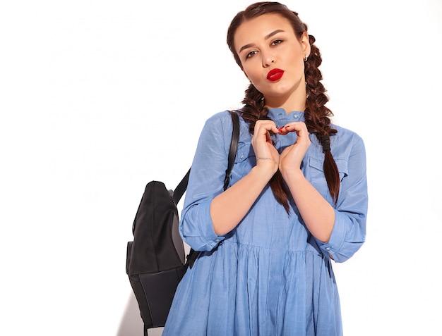 Porträt des jungen glücklichen lächelnden frauenmodells mit hellem make-up und den roten lippen mit zwei zöpfen in den händen im bunten blauen kleid und im rucksack des sommers lokalisiert. zeige herzschild