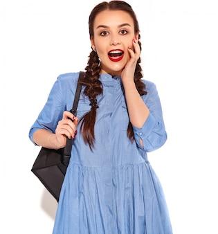 Porträt des jungen glücklichen lächelnden frauenmodells mit hellem make-up und den roten lippen mit zwei zöpfen in den händen im bunten blauen kleid und im rucksack des sommers lokalisiert