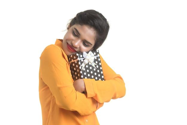 Porträt des jungen glücklichen lächelnden indischen mädchens, das geschenkboxen auf einer weißen wand hält.