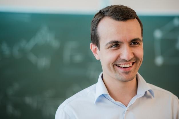 Porträt des jungen glücklichen lächelnden lehrers oder studentenmannes, der nahe tafelhintergrund steht