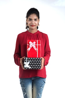 Porträt des jungen glücklichen lächelnden mädchens, das mit geschenkboxen auf einem weißen hintergrund hält und aufwirft.