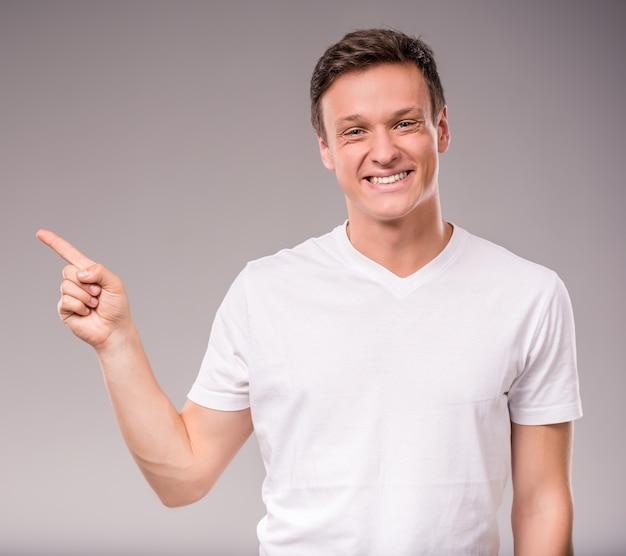 Porträt des jungen, glücklichen mannes, der mit seinem finger zeigt