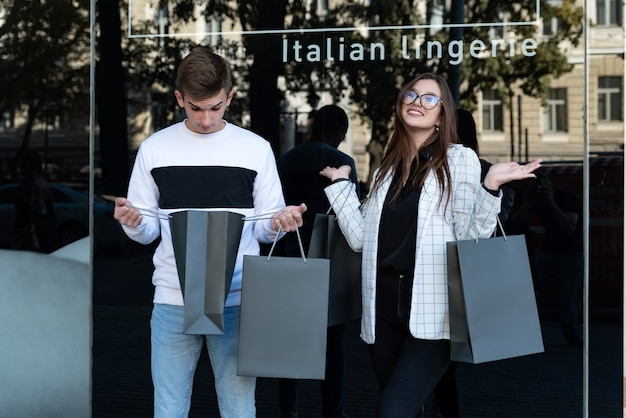 Porträt des jungen glücklichen paares mit einkaufstaschen. überraschter kerl, der in eine einkaufstasche schaut. schwarzer freitag. einkaufen.