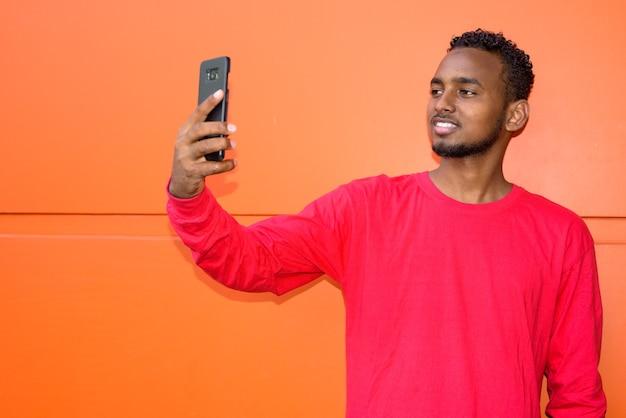 Porträt des jungen gutaussehenden afrikanischen bärtigen mannes mit afro-haaren gegen orange wand im freien