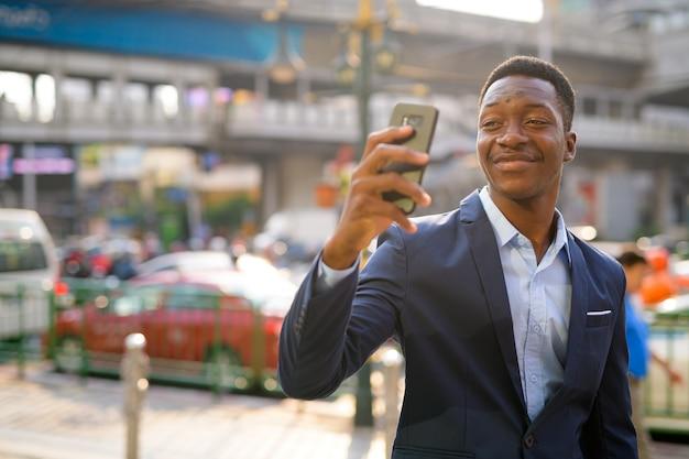 Porträt des jungen gutaussehenden afrikanischen geschäftsmannes, der die stadtstraßen von bangkok erkundet