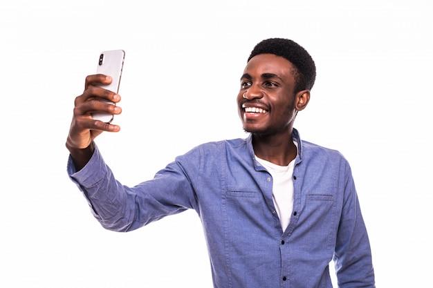 Porträt des jungen gutaussehenden afroamerikanischen mannes, der smartphone verwendet, um selfie-bilder und das lächeln zu nehmen, das gegen weiße wand steht