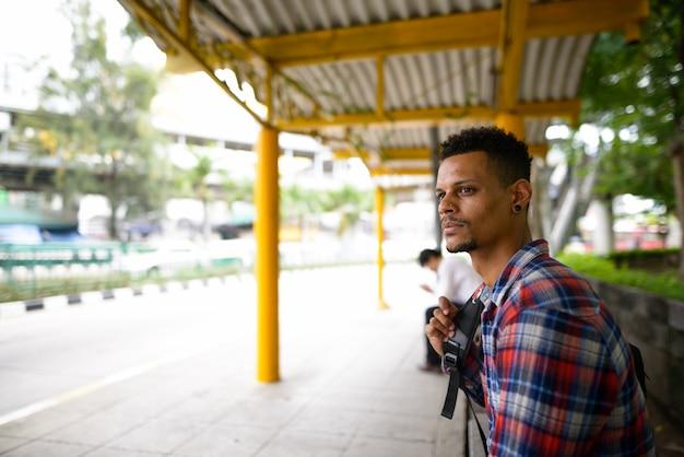 Porträt des jungen gutaussehenden bärtigen afrikanischen hipster-mannes als tourist mit rucksack, der an der bushaltestelle in der stadt draußen wartet