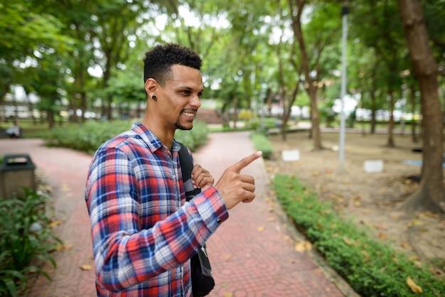 Porträt des jungen gutaussehenden bärtigen afrikanischen hipster-mannes am park im freien
