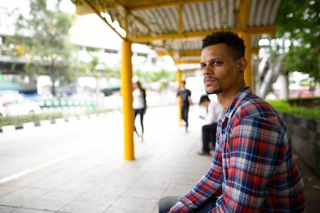 Porträt des jungen gutaussehenden bärtigen afrikanischen hipster-mannes, der an der bushaltestelle in der stadt draußen wartet