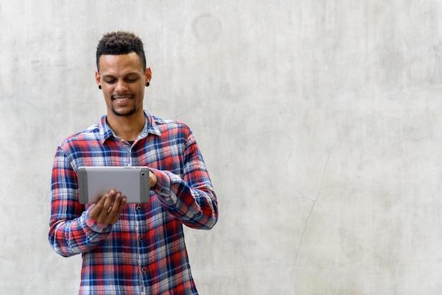 Porträt des jungen gutaussehenden bärtigen afrikanischen hipster-mannes gegen betonwand im freien