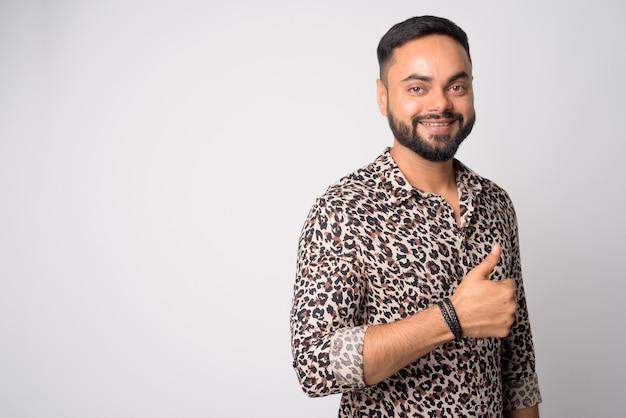 Porträt des jungen gutaussehenden bärtigen indischen mannes gegen weiße wand