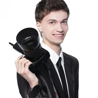 Porträt des jungen gutaussehenden fotografen, der die kamera hält. auf weiß isoliert