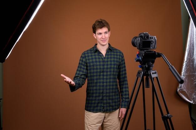 Porträt des jungen gutaussehenden hipster-mannes, der mit kamera vloggt