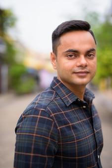 Porträt des jungen gutaussehenden indischen geschäftsmannes in den straßen draußen
