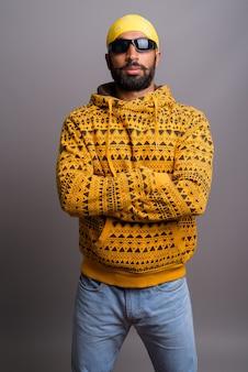 Porträt des jungen gutaussehenden indischen mannes, der kapuzenpulli trägt