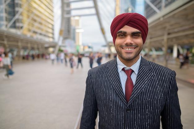 Porträt des jungen gutaussehenden indischen sikh-geschäftsmannes, der turban trägt, während die stadt bangkok, thailand erkundet