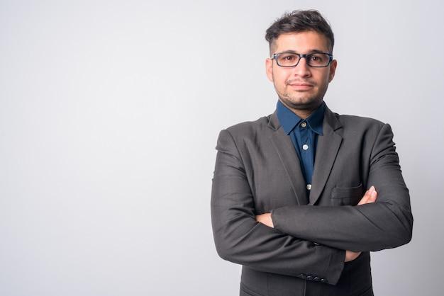 Porträt des jungen gutaussehenden iranischen geschäftsmannes im anzug, der brillen auf weiß trägt