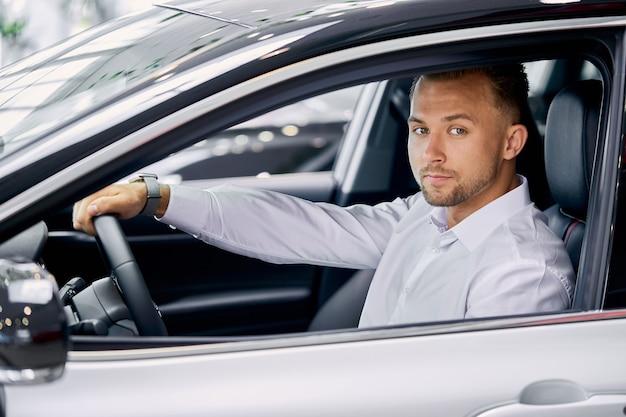 Porträt des jungen gutaussehenden kaukasischen kerls, der hinter dem lenkrad des neuen autos sitzt