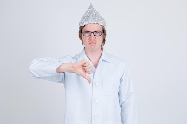 Porträt des jungen gutaussehenden mannarztes, der zinnfolienhut als verschwörungstheoriekonzept auf weiß trägt