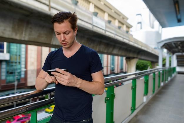 Porträt des jungen gutaussehenden mannes am himmelbahnhof in der stadt im freien