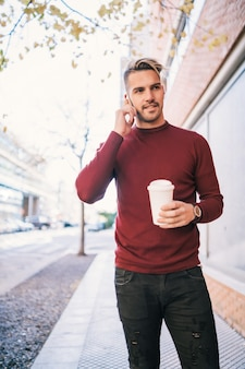 Porträt des jungen gutaussehenden mannes, der am telefon spricht, während eine tasse kaffee draußen in der straße hält. kommunikationskonzept.