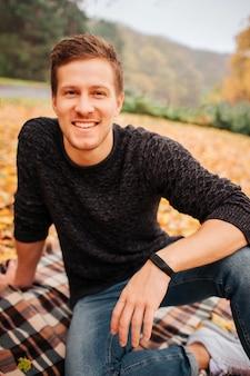 Porträt des jungen gutaussehenden mannes, der auf decke sitzt und gerade mit lächeln schaut. er stützt sich auf eine hand. guy posiert.
