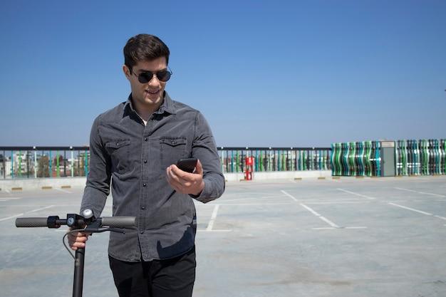 Porträt des jungen gutaussehenden mannes, der auf seinem elektroroller steht und sein smartphone betrachtet