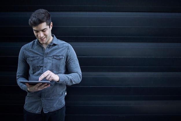 Porträt des jungen gutaussehenden mannes, der auf tablet-computer tippt und internet surft