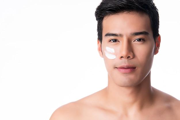 Porträt des jungen gutaussehenden mannes, der cremelotion auf gesicht aufträgt, lokalisiert