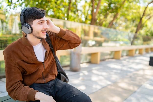 Porträt des jungen gutaussehenden mannes, der musik mit kopfhörern beim sitzen im freien hört. stadtkonzept.