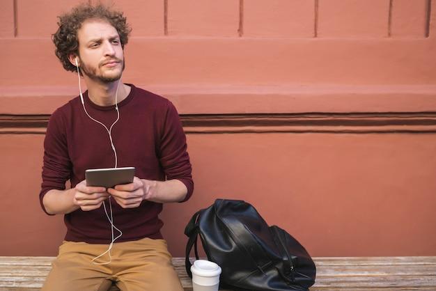 Porträt des jungen gutaussehenden mannes, der sein digitales tablett draußen in der straße benutzt. technologie und stadtkonzept.