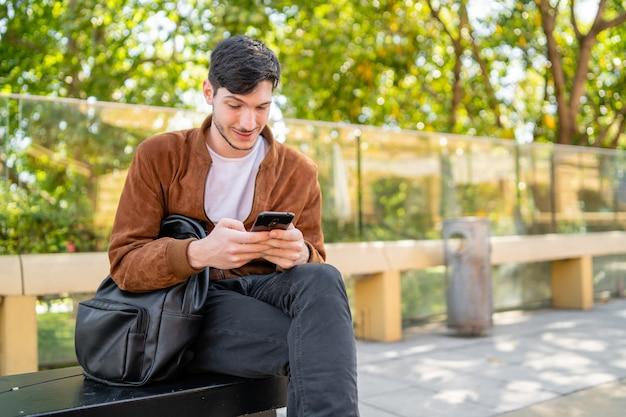 Porträt des jungen gutaussehenden mannes, der sein handy benutzt, während er draußen sitzt. kommunikation und stadtkonzept.