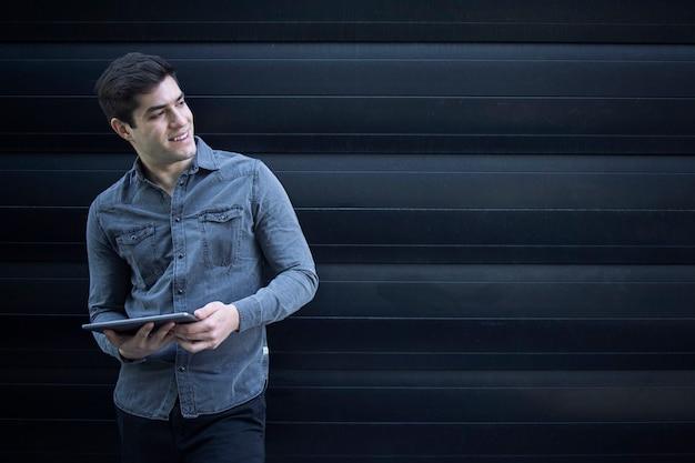 Porträt des jungen gutaussehenden mannes, der seinen tablet-computer hält und beiseite schaut