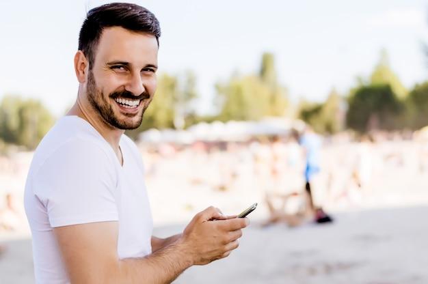 Porträt des jungen gutaussehenden mannes, der smartphone auf dem strand verwendet.