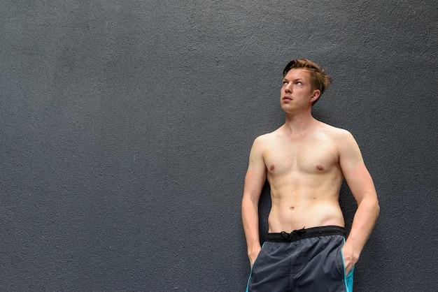 Porträt des jungen gutaussehenden mannes, der während des aufschauens gegen graue betonwand denkt