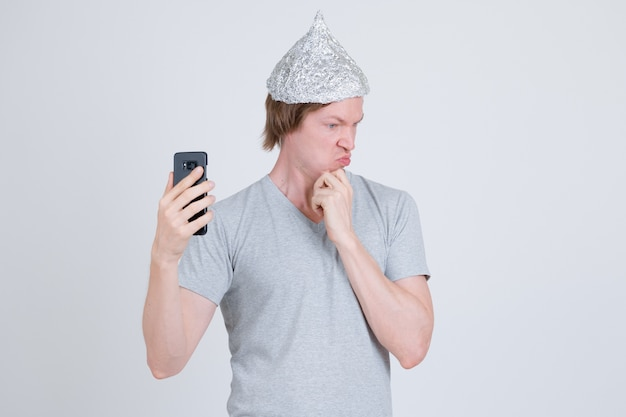 Porträt des jungen gutaussehenden mannes, der zinnfolienhut als verschwörungstheoriekonzept auf weiß trägt