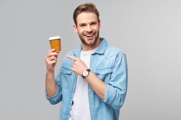 Porträt des jungen gutaussehenden mannes im jeanshemd über der hellen wand, die tasse kaffee hält, um zu gehen