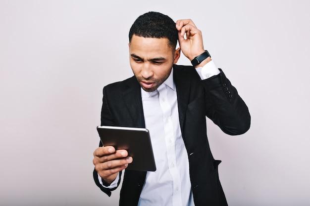 Porträt des jungen gutaussehenden mannes im weißen hemd und in der schwarzen jacke bei der arbeit mit tablette. modischer geschäftsmann, missverständnis, beschäftigt, erfolgreich, moderner lebensstil.