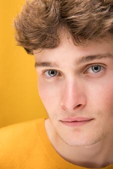Porträt des jungen gutaussehenden mannes in einer gelben szene