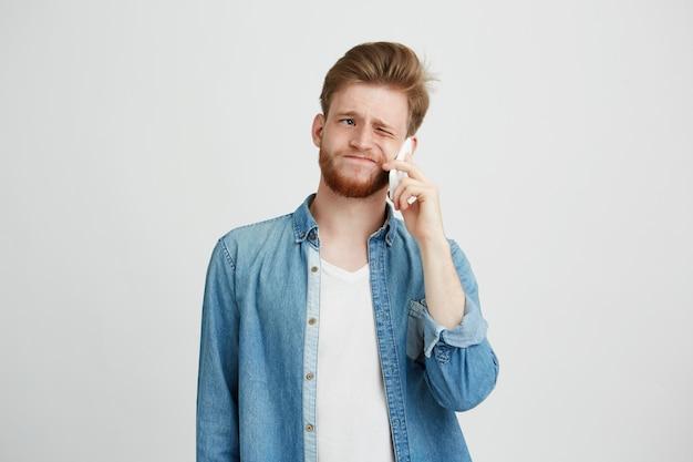 Porträt des jungen gutaussehenden mannes mit bart spricht nicht am telefon.
