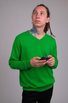 Porträt des jungen gutaussehenden mannes mit dreadlocks gegen weiße wand