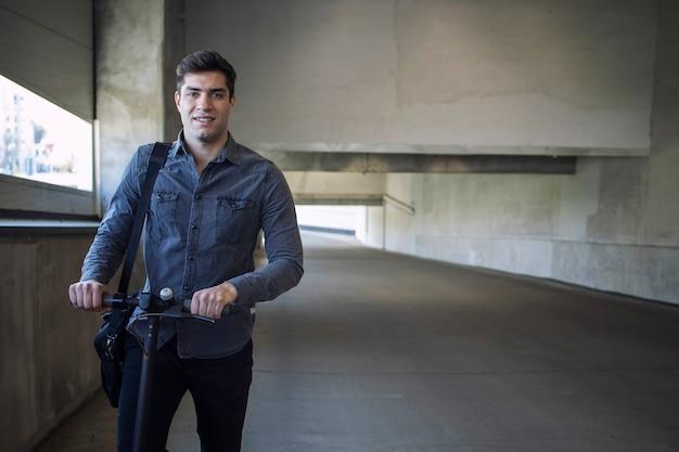 Porträt des jungen gutaussehenden mannes mit umhängetasche, die auf seinem elektroroller steht