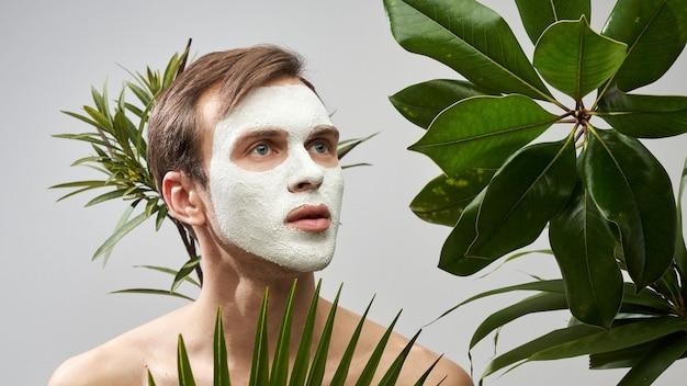 Porträt des jungen gutaussehenden mannes mit weißer kosmetischer maske auf seinem gesicht vor dem hintergrund der grünen pflanzen. gesichtspflege für männer