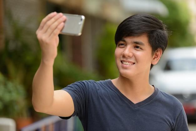 Porträt des jungen gutaussehenden philippinischen mannes in den straßen draußen