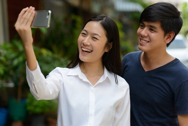 Porträt des jungen gutaussehenden philippinischen mannes und der jungen schönen asiatischen frau zusammen in den straßen draußen