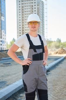 Porträt des jungen gutaussehenden positiven arbeiters, der weißen schutzhelm und arbeitsoveralls trägt, die an der baustelle stehen