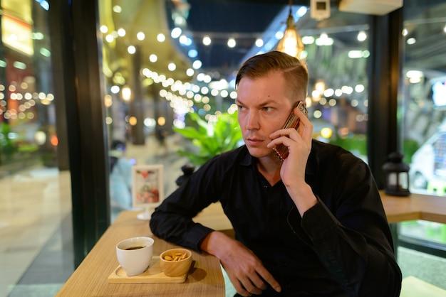 Porträt des jungen gutaussehenden skandinavischen geschäftsmannes, der am kaffeehaus entspannt