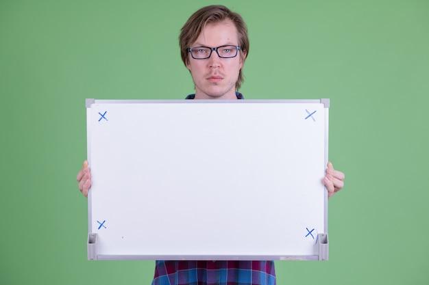 Porträt des jungen gutaussehenden skandinavischen hipster-mannes mit brille gegen chroma key oder grüne wand