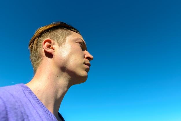 Porträt des jungen gutaussehenden skandinavischen mannes gegen klaren blauen himmel